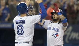Toronto Blue Jays' Freddy Galvis is met at home plate by Cavan Biggio after Galvis drove him in with a two-run home run during the fifth inning of the team's baseball game against the New York Yankees in Toronto on Tuesday, June 4, 2019. (Fred Thornhill/The Canadian Press via AP)