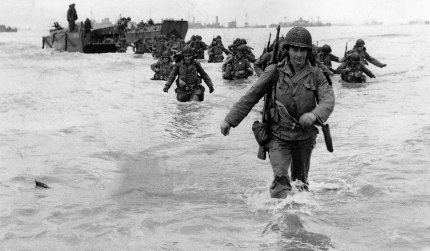 U.S. infantrymen wade through the surf as they land at Normandy in the days following the Allies' June 1944, D-Day invasion of occupied France. An allied ship loaded with supplies and reinforcements waits on the horizon.  (AP Photo/Bert Brandt)