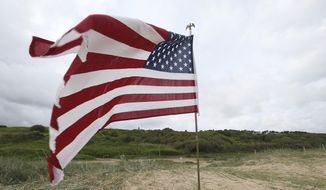 An American flag is planted on Omaha beach, Normandy, , Wednesday June 5, 2019. Extensive commemorations are being held in the U.K. and France to honor the nearly 160,000 troops from Britain, the United States, Canada and other nations who landed in Normandy on June 6, 1944 in history's biggest amphibious invasion. (AP Photo/David Vincent)