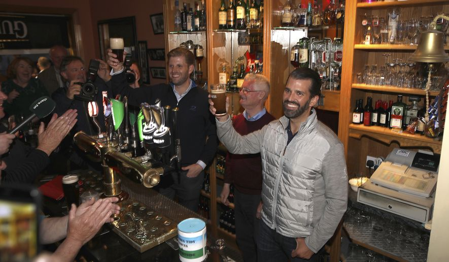 President Trump's sons Eric and Donald Jr., right, hold a pint of Guinness in a pub in Doonbeg west of Ireland Wednesday, June 5, 2019. President Trump is overnighting in Ireland before attending 75th anniversary of the D-Day landings events in northern France Thursday. (AP Photo/Peter Morrison)
