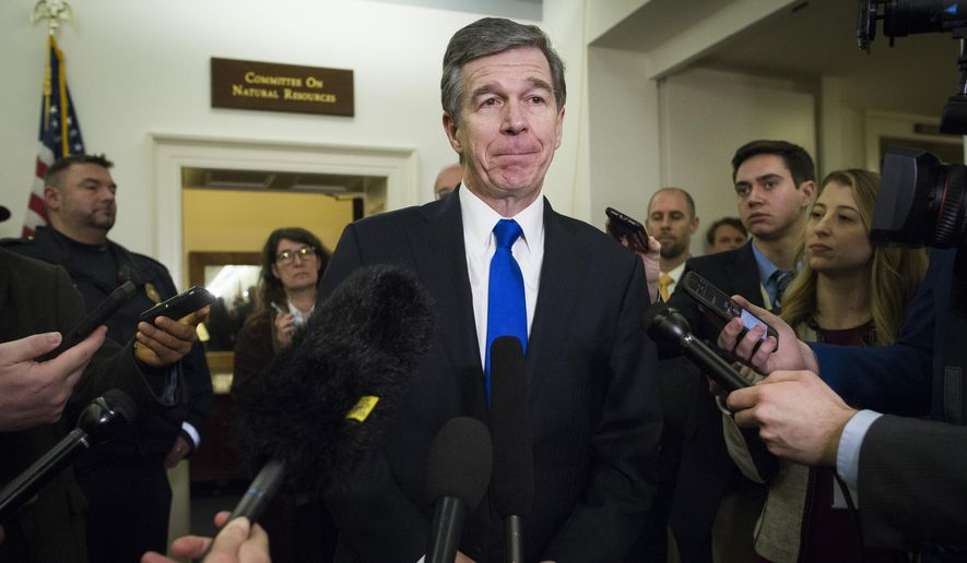 In a Feb. 6, 2019, file photo, North Carolina Gov. Roy Cooper speaks with reporters after testifying before the House Natural Resources Committee hearing on climate change, on Capitol Hill in Washington. (AP Photo/Cliff Owen) ** FILE **