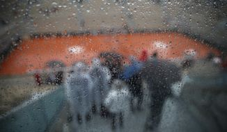 Rain drops trickle down a glass wall on center court where rain delayed the start of quarterfinal matches of the French Open tennis tournament at the Roland Garros stadium in Paris, Wednesday, June 5, 2019. (AP Photo/Christophe Ena)