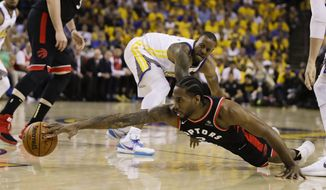Toronto Raptors forward Kawhi Leonard, foreground, reaches for the ball in front of Golden State Warriors forward Andre Iguodala during the first half of Game 3 of basketball's NBA Finals in Oakland, Calif., Wednesday, June 5, 2019. (AP Photo/Ben Margot) ** FILE **