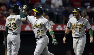 Oakland Athletics' Ramon Laureano (22) celebrates his two-run home run with teammates Jurickson Profar, left, and Robbie Grossman during the sixth inning of the team's baseball game against the Los Angeles Angels on Tuesday, June 4, 2019, in Anaheim, Calif. (AP Photo/Marcio Jose Sanchez)