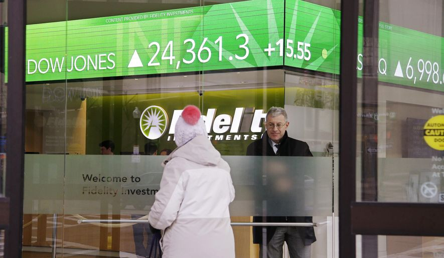 FILE - In this Feb. 6, 2018, file photo, a woman walks through the front doors at a Fidelity Investments office on Congress Street as the ticker displays stock market numbers in Boston. Federal regulators are moving to require that brokers provide their customers with detailed disclosures of their potential conflicts of interest when dispensing advice for retirement planning and other investments. (AP Photo/Stephan Savoia, File)