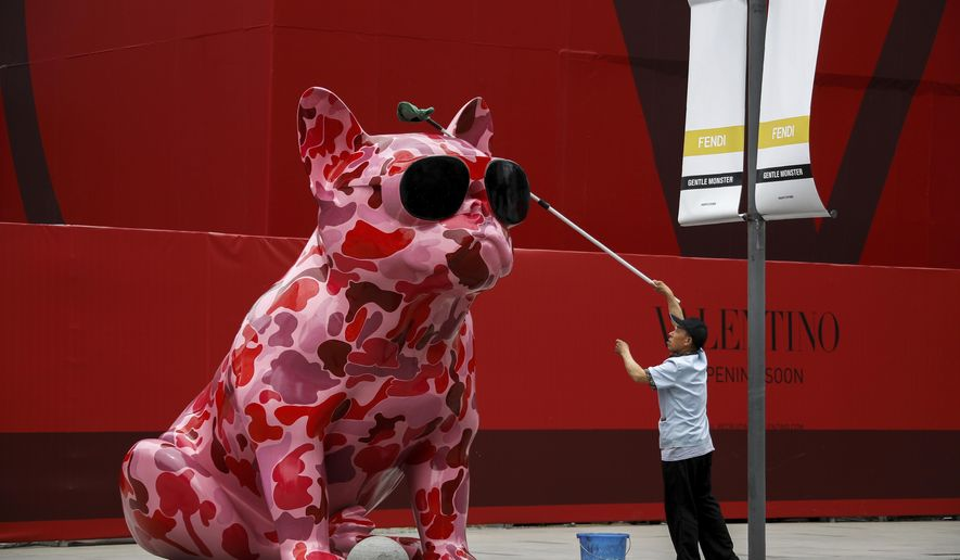A worker wipes a dog sculpture outside a luxury fashion boutique under construction at the capital city's popular shopping mall in Beijing, Wednesday, June 5, 2019. Amid the trade war with the United States, Chinese President Xi Jinping is expressing confidence in the resilience of the Chinese economy. (AP Photo/Andy Wong)