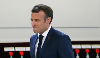 French president Emmanuel Macron arrives to deliver his speech to the French soccer team prior to to award them with the Legion d'Honneur (Officer of the Legion of Honor) during a ceremony at the Elysee Palace in Paris, Tuesday, June 4, 2019. (AP Photo/Francois Mori, pool)