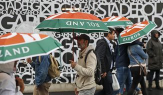 Spectators with umbrellas arrive for the quarterfinal matches of the French Open tennis tournament at the Roland Garros stadium in Paris, Wednesday, June 5, 2019. (AP Photo/Pavel Golovkin)