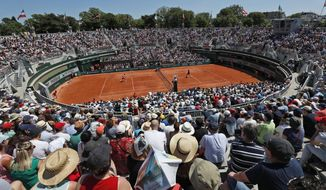 In this Saturday, June 1, 2019, image, spectators watch a tennis match at court 1 during third round match of the French Open tennis tournament at the Roland Garros stadium in Paris. When the French Open ends, its Court No. 1 will bid adieu, too, demolished to make way for a garden at Roland Garros. (AP Photo/Pavel Golovkin)