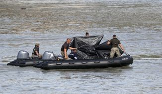 A rescue crew works on the Danube river where a sightseeing boat capsized in Budapest, Hungary, Wednesday, June 5, 2019. Divers and rescue crews slowly are recovering the bodies of a growing number of people killed when a sightseeing boat and a long river cruise ship collided in Hungary's capital. (AP Photo/Laszlo Balogh)