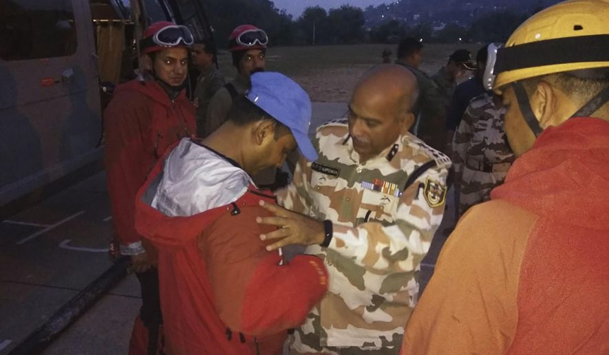 In this photo provided by the Indo Tibetan Border Police force or ITBP, a senior officer ITBP wishes best luck to the team of their soldiers before they set to leave to rescue and retrieve the bodies of international climbers, in Pithoragarh, Uttarakhand state, India, Wednesday, June 5, 2019. Indian officials are working on a plan to retrieve five bodies believed to be mountaineers from a team of international climbers that went missing on a notoriously dangerous Himalayan mountain. Local officials say all eight of the climbers that disappeared May 26 on Nanda Devi East are presumed dead, and the five bodies photographed by air Monday are thought to be from the missing expedition. The missing team includes four Britons, two Americans, an Australian and an Indian liaison officer. (Indo Tibetan Border Police force via AP)