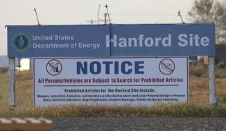 FILE - In this May 9, 2017, file photo, signs are posted at an entrance to the Hanford Nuclear Reservation in Richland, Wash.The state of Washington believes the federal government is unlikely to meet legal deadlines for emptying underground tanks holding radioactive waste at Hanford. The state Department of Ecology says it is prepared to take the U.S. Department of Energy back to federal court to get the cleanup back on track. (AP Photo/Manuel Valdes, File)