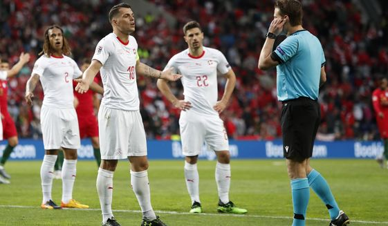Switzerland's Granit Xhaka, second left, argues with referee Felix Brych, right, as he checking a VAR during the UEFA Nations League semifinal soccer match between Portugal and Switzerland at the Dragao stadium in Porto, Portugal, Wednesday, June 5, 2019. (AP Photo/Armando Franca)