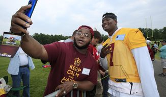 Washington Redskins quarterback Dwayne Haskins Jr., right, poses for a selfie with Redskins fan Davon Adams, from Washington, following an NFL football minicamp at Redskins Park in Ashburn, Va., Wednesday, June 5, 2019. (AP Photo/Manuel Balce Ceneta)