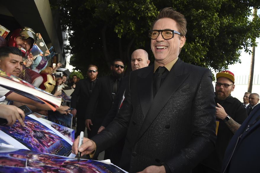 """FILE - In this April 22, 2019, file photo Robert Downey Jr. signs autographs as he arrives at the premiere of """"Avengers: Endgame"""" at the Los Angeles Convention Center. After playing Iron Man for more than a decade, Robert Downey Jr. has found a real-life villain he wants to defeat: pollution. The movie star says he plans to start an organization next year called the Footprint Coalition. (Photo by Chris Pizzello/Invision/AP, File)"""