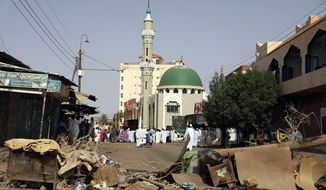 Worshippers gather at a mosque behind a roadblock set by protesters on a main street in the Sudanese capital Khartoum to stop military vehicles from driving through the area on Wednesday, June 5, 2019. The death toll in Sudan amid a violent crackdown on pro-democracy protesters and the dispersal of their peaceful sit-in earlier this week in the capital climbed on Wednesday, protest organizers said. (AP Photo)