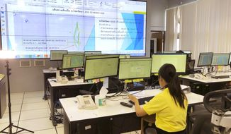 In this May 21, 2019, photo, staff monitor fishing vessels in real time at a state-of-the-art surveillance center in Bangkok, one of seven in the Asia-Pacific region. The centers help to enforce the Port State Measures Agreement, which aims to help curb illegal, unreported and unregulated, or IUU, fishing. UN officials are urging more governments to join the agreement to help combat IUU fishing, which costs world fisheries more than $20 billion a year. (AP Photo/Elaine Kurtenbach)