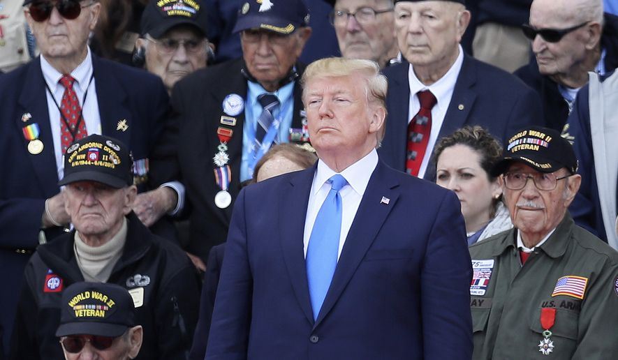 U.S. President Donald Trump stands with World War II veterans during a ceremony to mark the 75th anniversary of D-Day at the Normandy American Cemetery in Colleville-sur-Mer, Normandy, France, Thursday, June 6, 2019. World leaders are gathered Thursday in France to mark the 75th anniversary of the D-Day landings. (AP Photo/David Vincent)