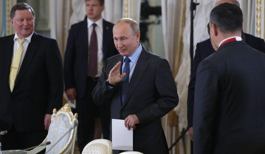 Russian President Vladimir Putin, center, arrives to attend a meeting with international investors community at the St. Petersburg International Economic Forum in St. Petersburg, Russia, Thursday, June 6, 2019. (Yuri Kochetkov/Pool Photo via AP)