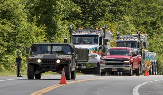 Military police direct traffic along Route 293 near the site where an armored personnel vehicle overturned killing at least one person, Thursday, June 6, 2019, in Cornwall, N.Y. West Point officials say one cadet was killed and over a dozen people were injured when a vehicle they were riding in for summer training overturned. The accident occurred near Camp Natural Bridge, an area where cadet summer training takes place. (AP Photo/Allyse Pulliam)