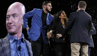 Security removes a protestor, second from left, from the stage as Amazon CEO Jeff Bezos speaks at the the Amazon re:MARS convention, Thursday, June 6, 2019, in Las Vegas. (AP Photo/John Locher)