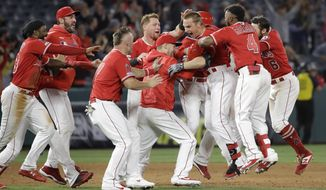Los Angeles Angels' Dustin Garneau, third from right, is mobbed by teammates after driving in the game-winning run with a double during the ninth inning of a baseball game against the Oakland Athletics Wednesday, June 5, 2019, in Anaheim, Calif. Los Angeles won 10-9. (AP Photo/Marcio Jose Sanchez)