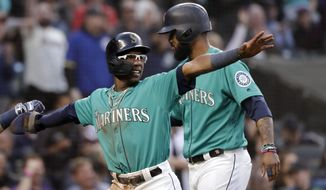 Seattle Mariners' Shed Long, left, heads to the dugout with Domingo Santana after the two scored against the Houston Astros, and points to first base to acknowledge the single of Mallex Smith that scored the two in the fifth inning of a baseball game Wednesday, June 5, 2019, in Seattle. (AP Photo/Elaine Thompson)