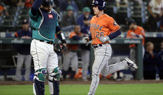 Seattle Mariners catcher Omar Narvaez, left, looks down as Houston Astros' Myles Straw scores during the 14th inning of a baseball game Thursday, June 6, 2019, in Seattle. (AP Photo/Elaine Thompson)