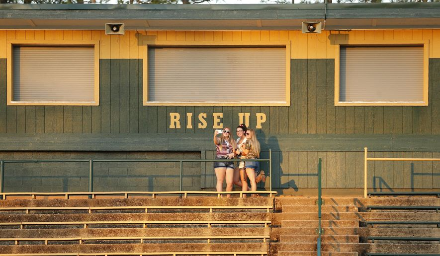 Paradise High School students pose for a selfie at the school's football field in Paradise, Calif., Wednesday, June 5, 2019. Many students of Paradise High lost their homes when the Camp Fire swept through the area and the school was forced to hold classes in Chico. (AP Photo/Rich Pedroncelli)