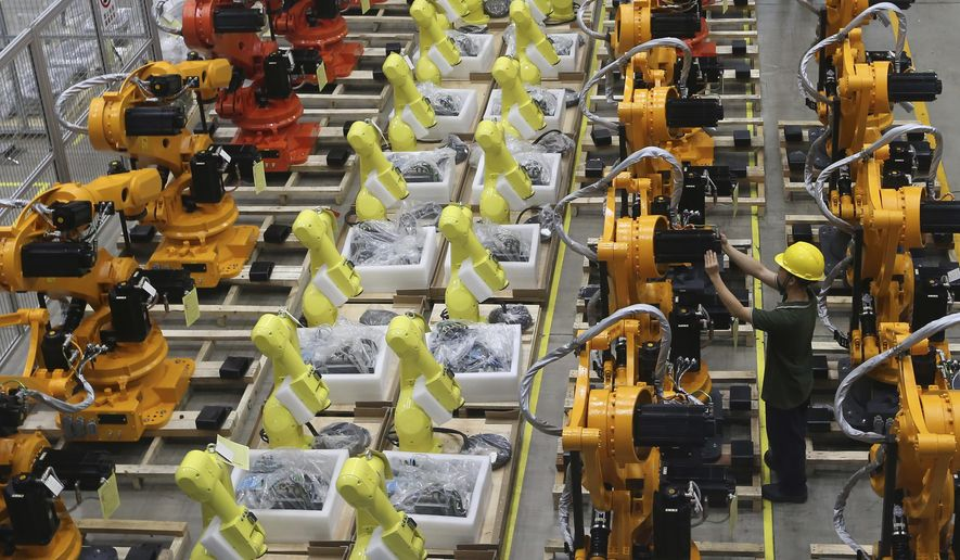 A worker checks on robot arms at a factory in Nanjing in east China's Jiangsu province, Thursday, June 6, 2019. (Chinatopix via AP) ** FILE **