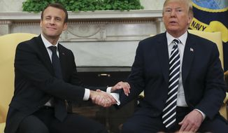 FILE - In this April 24, 2018, file photo, French President Emmanuel Macron winks to members of the media during his meeting with President Donald Trump in the Oval Office at the White House in Washington. Trump and Macron enjoy putting on a show of exaggerated handshakes, kisses and taps on the back, but they disagree on key issues, including climate change, Iran and world trade. (AP Photo/Pablo Martinez Monsivais, File)