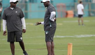 Miami Dolphins general manager Chris Grier, left, talks with head coach Brian Flores at the team's NFL football training facility, Tuesday, June 4, 2019, in Davie, Fla. (AP Photo/Lynne Sladky)