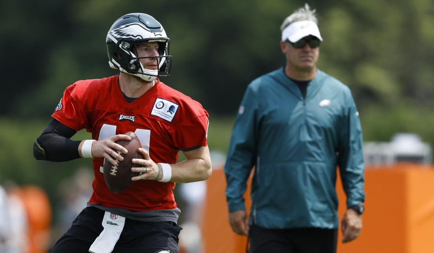 Philadelphia Eagles' Carson Wentz, left, participates in a drill as head coach Doug Pederson looks on during organized team activities at the NFL football team's practice facility, Wednesday, June 5, 2019, in Philadelphia. (AP Photo/Matt Slocum)