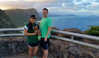 In this Dec. 2016 photo provided by Tracey Calanog shows Michelle Paul and David Paul, along with their dog Zooey, in Hawaii. The couple from Texas died while vacationing in Fiji. Health officials in Fiji say they don't yet have an answer on why a Texas couple died while vacationing on the island, but say influenza has been ruled out as a potential cause. Michelle Paul's father, Marc Calanog said that he got a call that Michelle was dead on May 25, 2019, and that David Paul was dead two days later. (Tracey Calanog via AP)