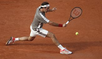 Switzerland's Roger Federer plays a shot against Switzerland's Stan Wawrinka during their quarterfinal match of the French Open tennis tournament at the Roland Garros stadium in Paris, Tuesday, June 4, 2019. (AP Photo/Jean-Francois Badias)