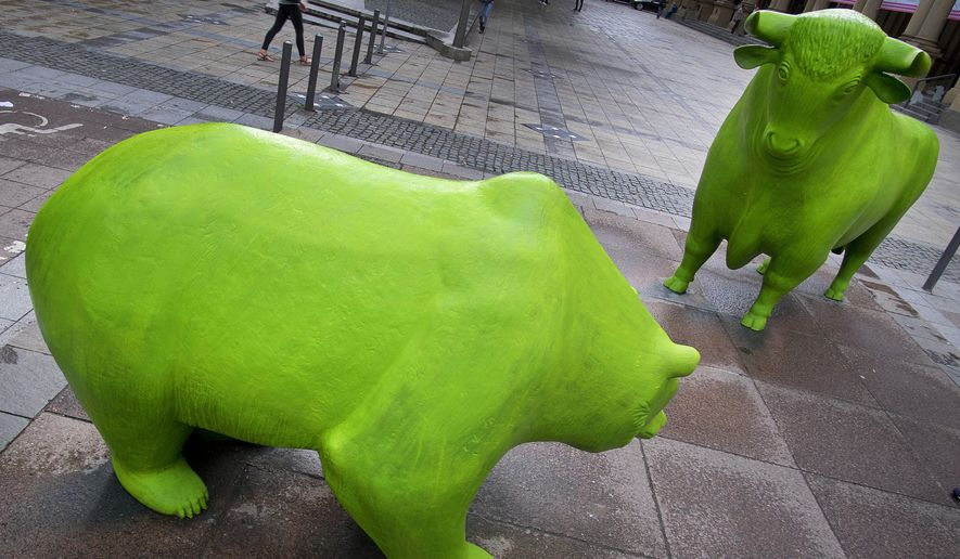 """The bull and bear in front of the stock market are painted all green in Frankfurt, Germany, Monday, June 3, 2019. They were painted on occasion of the upcoming """"Green Sauce"""" week when Frankfurt celebrates its most popular dish. (AP Photo/Michael Probst)"""