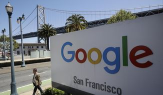 In this May 1, 2019, file photo a man walks past a Google sign outside with a span of the Bay Bridge at rear in San Francisco.  (AP Photo/Jeff Chiu, File) **FILE**