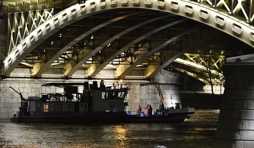 A boat taking part in the rescue operations is anchored under Margaret Bridge in Budapest, Hungary, Wednesday, June 5, 2019. A sightseeing boat carrying 33 South Korean tourists was crashed by a large river cruise ship and sank in the River Danube at a pier of Margaret Bridge on May 29, killing at least seven tourists. Seven other tourists were injured, 21 persons, including the two crew members, went missing. (Zoltan Mathe/MTI via AP)