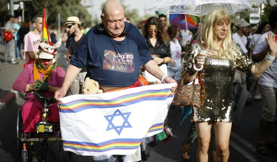 Participants hold flags during the annual Gay Pride parade in Jerusalem, Thursday, June 6, 2019. Thousands of people are marching through the streets of Jerusalem in the city's annual gay pride parade, a festival that exposes deep divisions between Israel's secular and Jewish ultra-Orthodox camps. (AP Photo/Ariel Schalit)