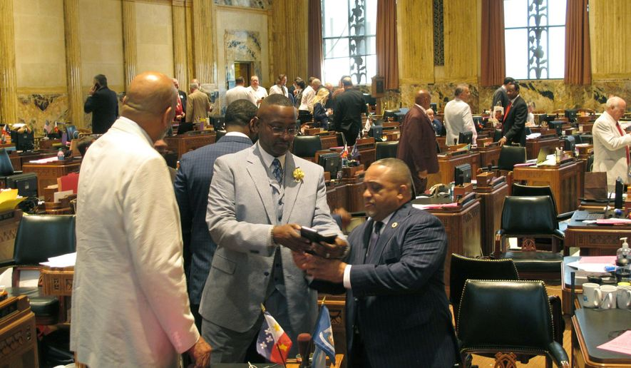 Rep. Vincent Pierre, D-Lafayette, right, looks at a phone with Reps. Patrick Jefferson, D-Homer, center, and Terry Landry, D-New Iberia, on the final day of the legislative session on Thursday, June 6, 2019, in Baton Rouge, La. (AP Photo/Melinda Deslatte)