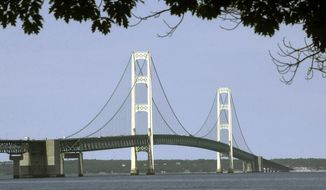 FILE - This July 19, 2002, file photo, shows the Mackinac Bridge that spans the Straits of Mackinac from Mackinaw City, Mich. Enbridge Inc. is asking a Michigan court to rule on the legality of an agreement it reached with former Gov. Rick Snyder to build an oil pipeline beneath the channel linking lakes Huron and Michigan. The Canadian company said Thursday, June 6, 2019 it is asking the Michigan Court of Claims to determine the constitutional validity of the deal. The Court of Claims deals with civil actions filed against the state and its agencies. (AP Photo/Carlos Osorio, File)
