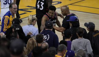Toronto Raptors guard Kyle Lowry, middle, gestures next to referee Marc Davis (8) near the front row of fans during the second half of Game 3 of basketball's NBA Finals between the Golden State Warriors and the Raptors in Oakland, Calif., Wednesday, June 5, 2019. A fan seated courtside for Game 3 of the NBA Finals was ejected after shoving Lowry when the Raptors star crashed into a row of seats while trying to save a ball from going out of bounds on Wednesday night. (AP Photo/Tony Avelar) ** FILE **