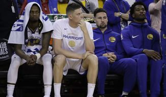 Golden State Warriors' Alfonzo McKinnie, from left, sits on the bench with Jonas Jerebko, Klay Thompson and Damian Jones during the second half of Game 3 of basketball's NBA Finals against the Toronto Raptors in Oakland, Calif., Wednesday, June 5, 2019. (AP Photo/Ben Margot)