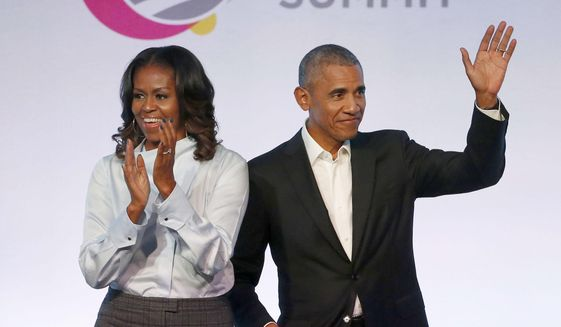 In this Oct. 31, 2017, file photo, former President Barack Obama, right, and former first lady Michelle Obama appear at the Obama Foundation Summit in Chicago. The couple's production company is teaming up with Spotify to produce exclusive podcasts for the platform. (AP Photo/Charles Rex Arbogast, File)