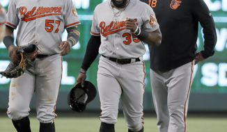 Baltimore Orioles' Hanser Alberto (57) and manager Brandon Hyde, right, walk in from the outfield with left fielder Dwight Smith Jr. after Smith hit the wall hard while catching a fly ball by Texas Rangers' Rougned Odor during the fourth inning of a baseball game in Arlington, Texas, Thursday, June 6, 2019. (AP Photo/Tony Gutierrez)