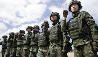 In this May 30, 2019, photo, the first team of Taiwan artillerywomen poses for the press during the annual Han Kuang exercises in Pingtung County, Southern Taiwan. Taiwan has confirmed Thursday, June 6, 2019, that it has asked to purchase more than 100 U.S. tanks, along with air defense and anti-tank missile systems in a major potential arms sale that could worsen frictions between Washington and Beijing. (AP Photo/Chiang Ying-ying) **FILE**
