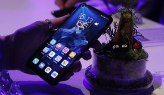 In this Tuesday, May 21, 2019, file photo, a member of the media tries out new Huawei Honor 20 series of phones following their global launch in London. Facebook has stopped letting its apps come pre-installed on smartphones sold by Huawei to comply with U.S. restrictions, dealing a fresh blow to the Chinese tech giant. The social network said Friday, June 7, it suspended providing software for Huawei to put on its devices while it reviews recently introduced U.S. sanctions. (AP Photo/Alastair Grant, file)