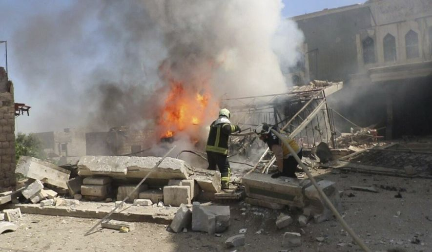 This photo posted May 28, 2019, and provided by the Syrian Civil Defense White Helmets, which has been authenticated based on its contents and other AP reporting, shows Syrian White Helmet civil defense workers trying to extinguish fire following an airstrike by Syrian government forces that targeted a health facility in the town of Kfar Nubul, southern Idlib, Syria. (Syrian Civil Defense White Helmets via AP, File)