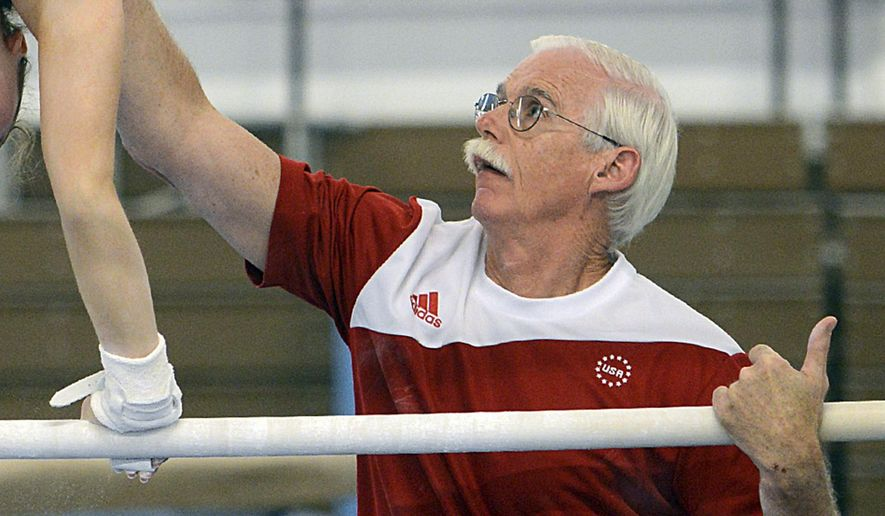 CORRECTS TO MISCONDUCT ALLEGATIONS AND REMOVES GYMNAST REFERENCE - In this June 30, 2016 photo, coach John Holman works with a gymnast at Parkettes National Gymnastics Training Center in Allentown, Pa. Holman, who has coached for about 40 years at Parkettes Gymnastics Club, has been barred by USA Gymnastics from being around minors unsupervised while it investigates a misconduct claim. USA Gymnastics tells The Allentown Morning Call that Holman's suspension, issued by the U.S. Center for SafeSport, is a requirement when such allegations are reported. (Emily Paine/The Morning Call via AP)