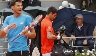 Austria's Dominic Thiem, left, and Serbia's Novak Djokovic head to the locker room as rain interrupted their semifinal match of the French Open tennis tournament at the Roland Garros stadium in Paris, Friday, June 7, 2019. (AP Photo/Michel Euler)